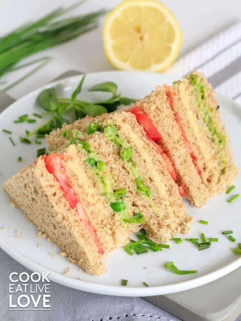 triple decker veggie sandwich on white plate with chives around it