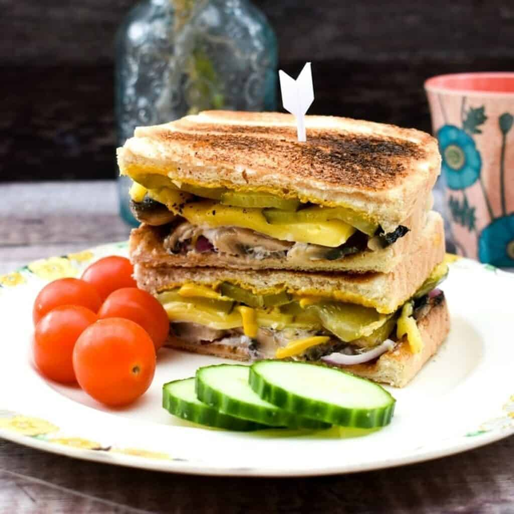 two halves of Cuban sandwiches on top of each other on plate with tomatoes and cucumbers in front of it
