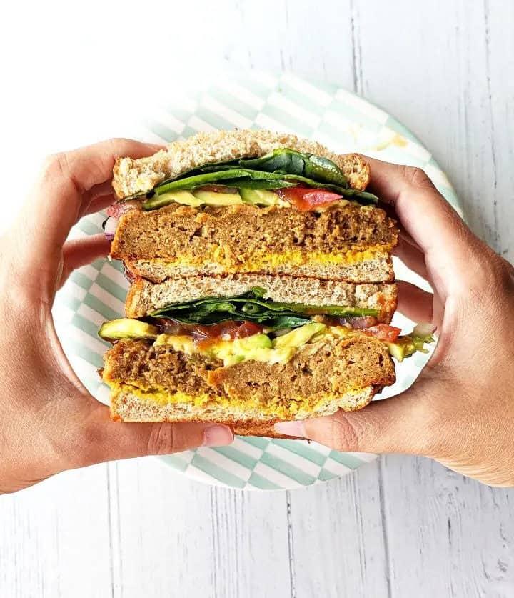 hands holding up seitan sandwich over a plate