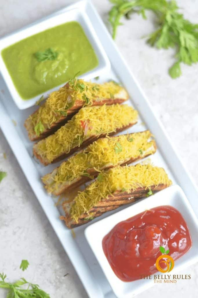 masala vegetable sandwiches on a white serving dish with dipping sauces