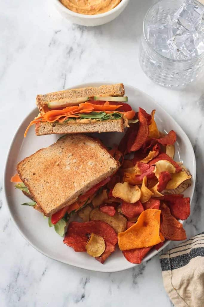 veggie hummus sandwich on white plate with vegetable chips on the side
