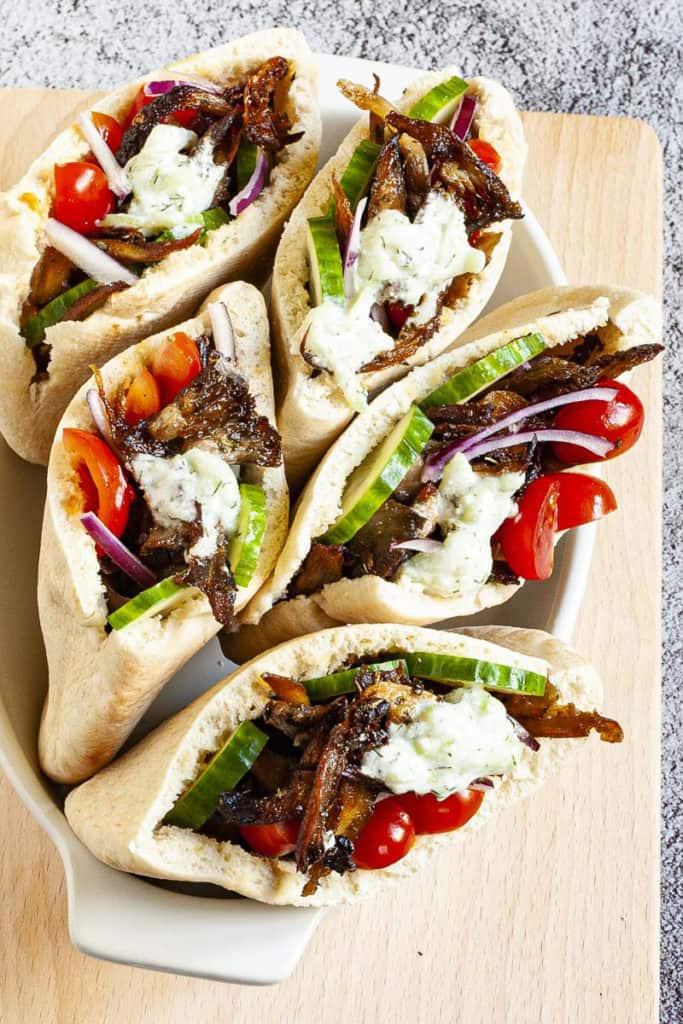vegan gyros in white serving dish topped with tzatziki sauce