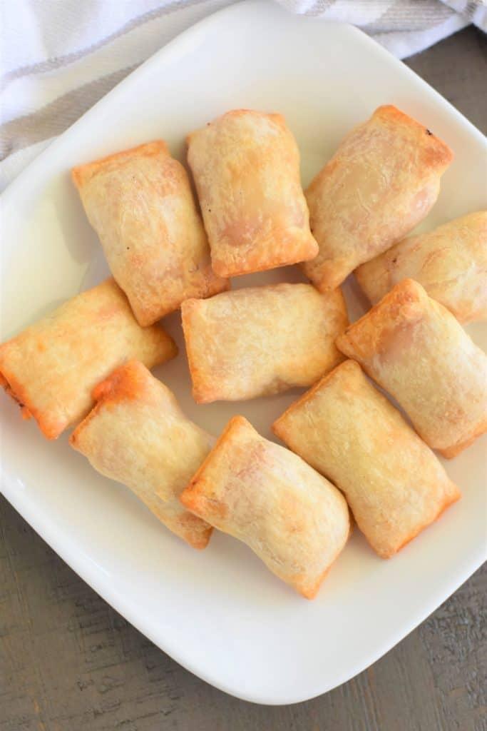overhead of gluten-free pizza rolls on white plate