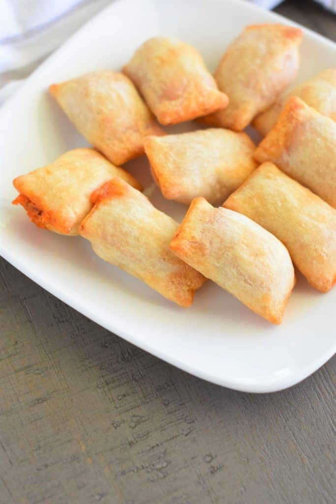 front view of gluten free pizza rolls on white plate