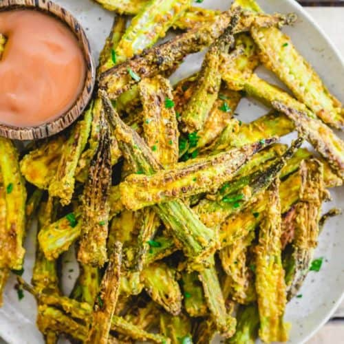 air fryer okra on white plate with side of dipping sauce