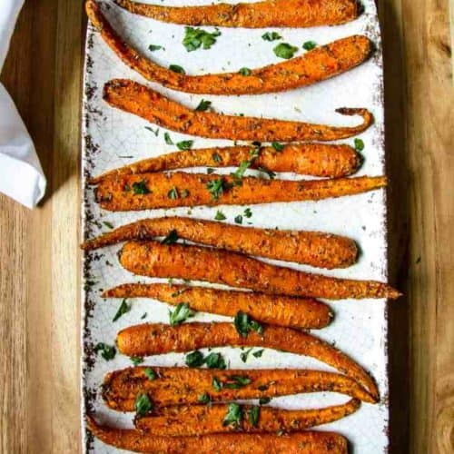 overhead of air fryer carrots on serving platter garnished with parsley
