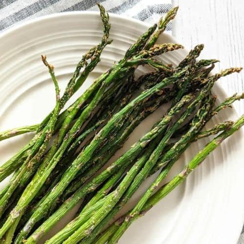 overhead of air fryer asparagus on white plate