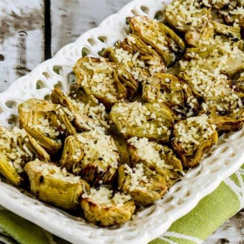 air fryer artichokes on white serving platter on green kitchen towel