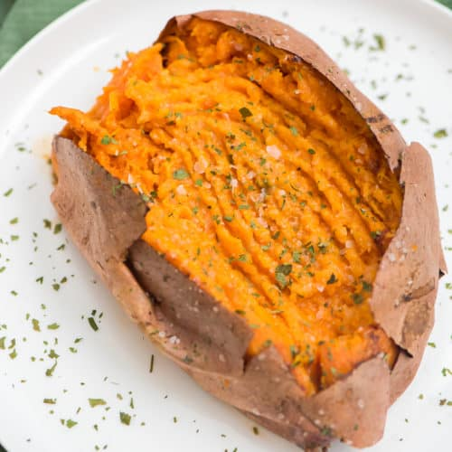 air fryer sweet potato on a white plate topped with sea salt and parsley