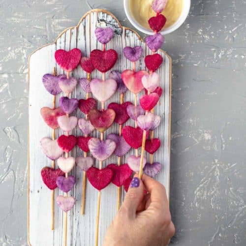 radish heart wands on white wooden board with hand taking one and dipping it into dipping sauce