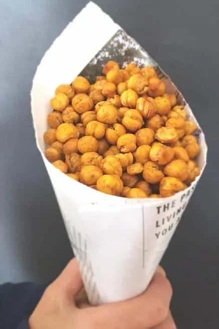 holding paper cone filled with spicy roasted chickpeas