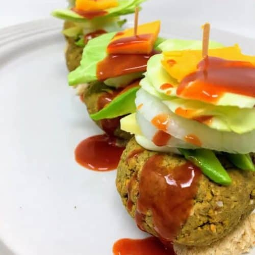 lentil sliders topped with avocado, onion, lettuce and vegan cheese
