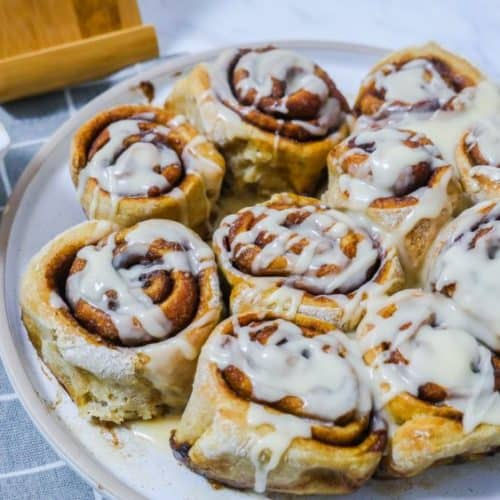 cinnamon rolls topped with icing on a white plate