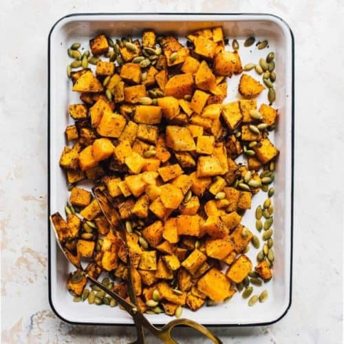 air fryer butternut squash in serving dish with serving tongs