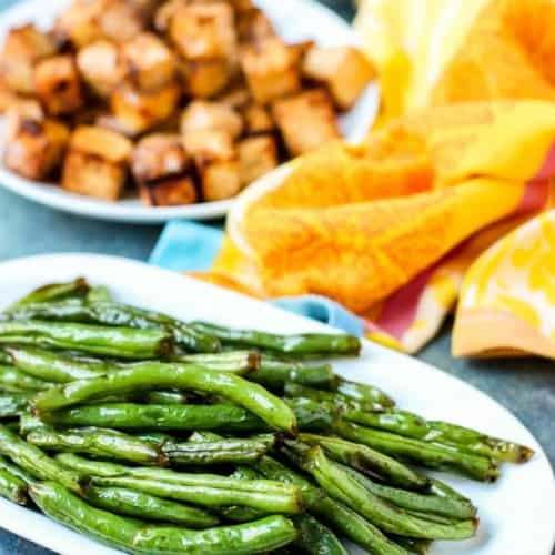 white plate with green beans with plate of tofu blurred out behind it