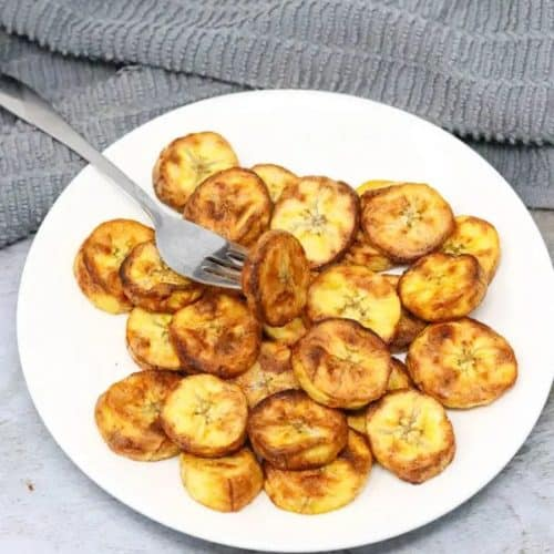 air fryer sweet plantains on white plate with a fork in one of them