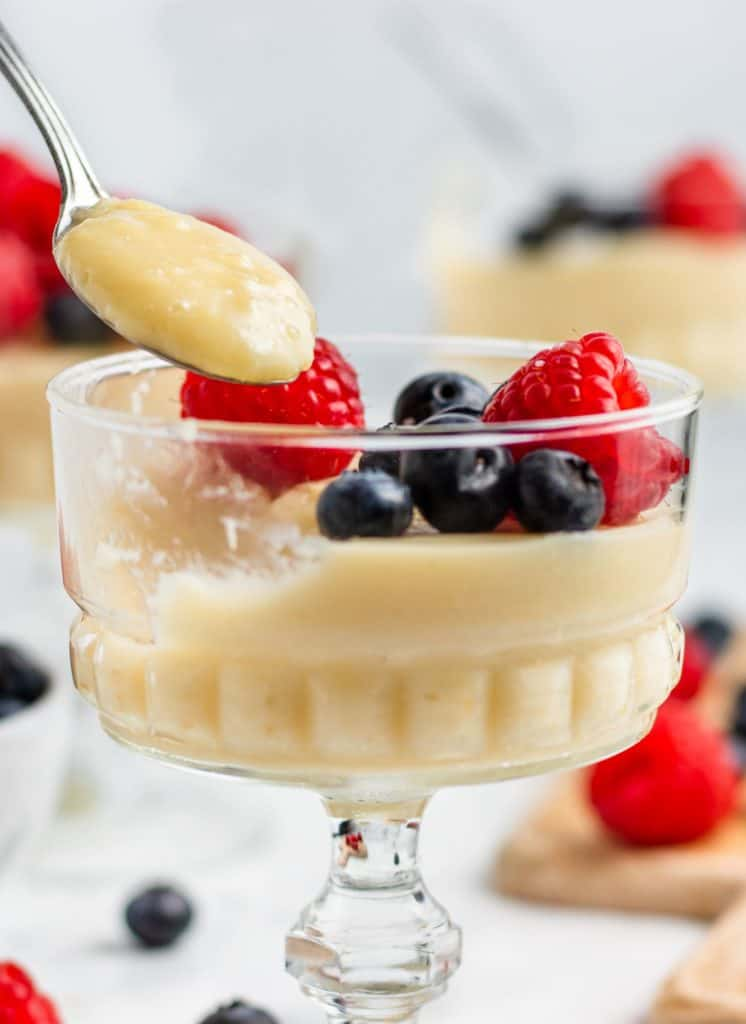 scooping out a spoonful of pudding in a glass container with berries on top and around it