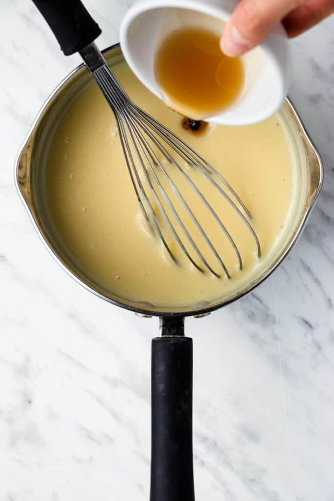 adding vanilla into the mixture in the saucepan